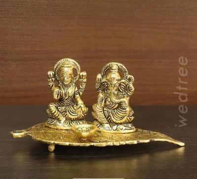 White metal gold finish Lakshmi Ganesha with diya on leaf return gift